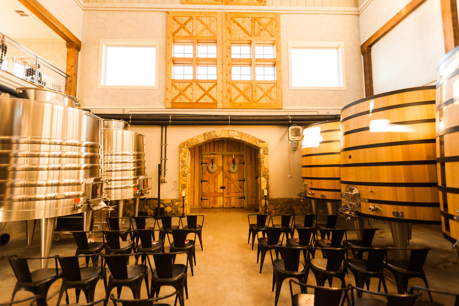 warm inviting winery tank room wedding ceremony