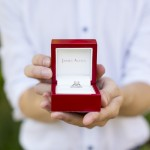 groom holding classic red engagement ring box