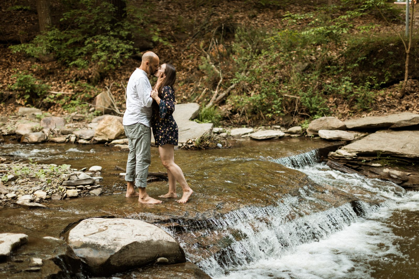 couple kissing in a stream in the woods in Letchworth New York