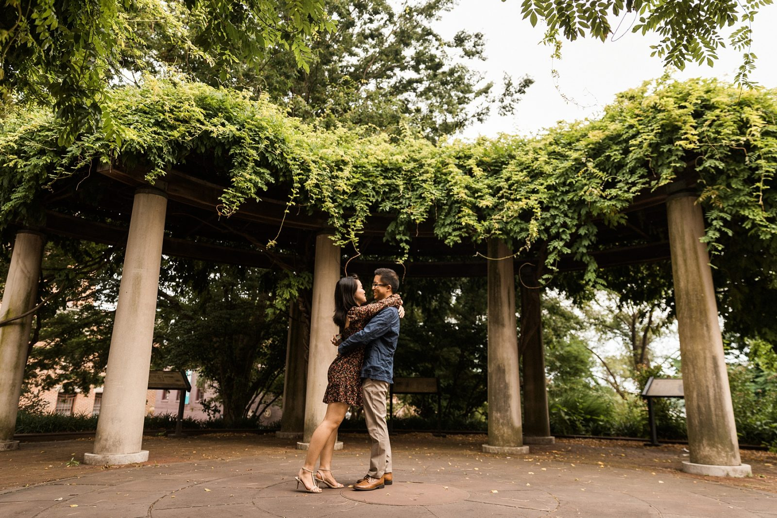 young asian couple gets engaged in a romantic garden setting with vine covered columns